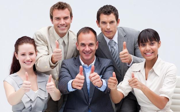 Szczęśliwa biznes drużyna z aprobatami
