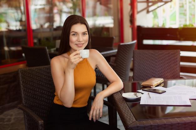 Szczęśliwa biznesowa kobieta pije kawę z rozrzuconymi papierami na stole. dobre wieści, radość i szczęście.