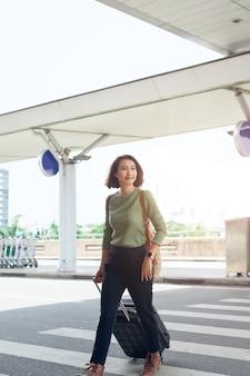 Szczęśliwa biznesowa kobieta podróżuje z bagażem na lotnisku