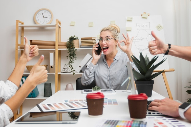 Szczęśliwa biznesowa kobieta pokazuje ok znaka