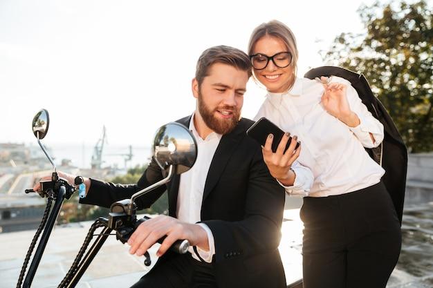 Szczęśliwa biznesowa kobieta stoi blisko brodatego mężczyzna w kostiumu