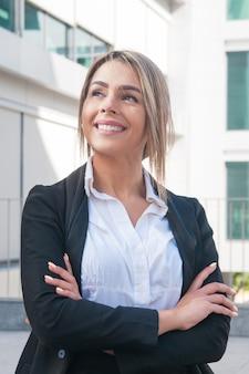 Szczęśliwa biznesowa kobieta stoi outdoors