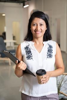 Szczęśliwa biznesowa kobieta trzyma kawę