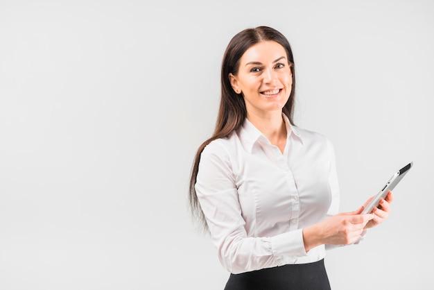 Szczęśliwa biznesowa kobieta używa pastylkę