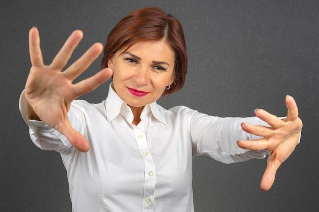 Szczęśliwa biznesowa kobieta w białej koszuli z rozpostartymi ramionami.