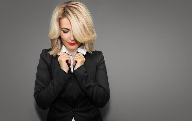 Szczęśliwa biznesowa kobieta w czarną kurtkę i czerwone usta.