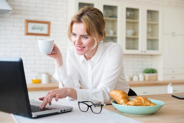 Szczęśliwa biznesowa kobieta z kawowym używa laptopem
