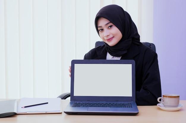 Szczęśliwa biznesowa młoda kobieta trzyma laptopa na biurku