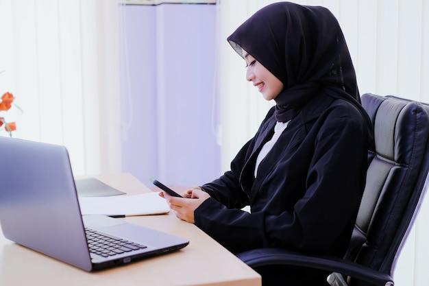 Szczęśliwa biznesowa młoda kobieta trzyma telefon komórkowy w biurze