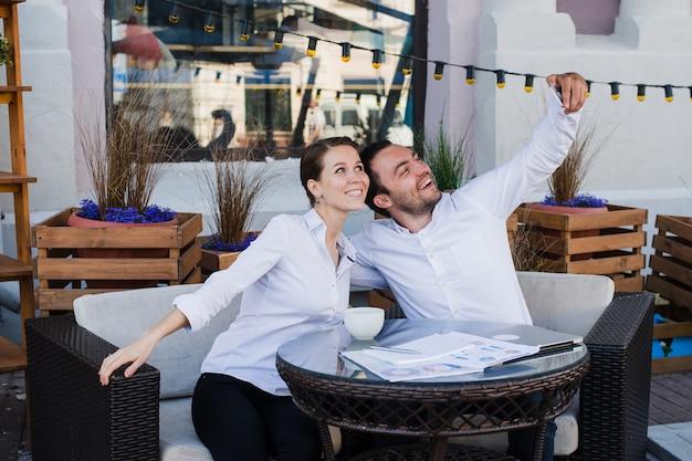 Szczęśliwa biznesowa para bierze selfie przy plenerową restauracją