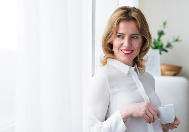 Szczęśliwa biznesowej kobiety pozycja z filiżanką
