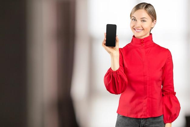Szczęśliwa bizneswoman pozycja w jej biurze i używać telefonie