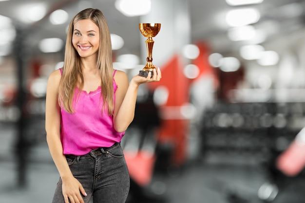 Szczęśliwa bizneswoman utrzymuje złotą filiżankę