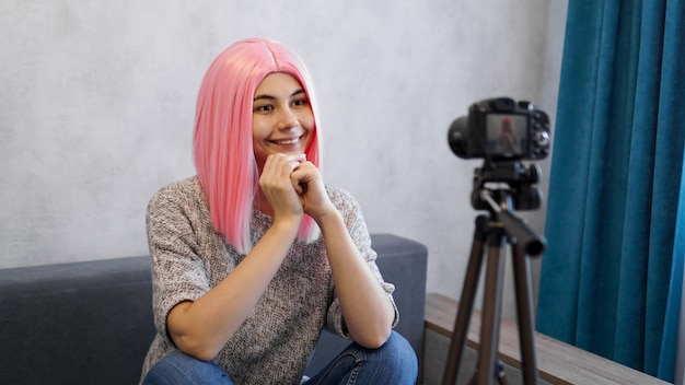 Szczęśliwa blogerka dziewczyna w różowej peruce przed aparatem na statywie. prowadzi blog wideo