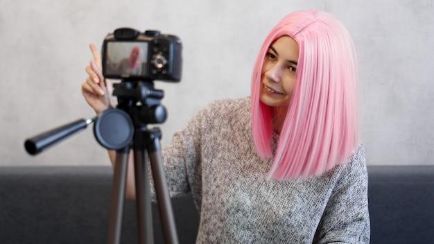 Szczęśliwa blogerka dziewczyna w różowej peruce przed aparatem na statywie