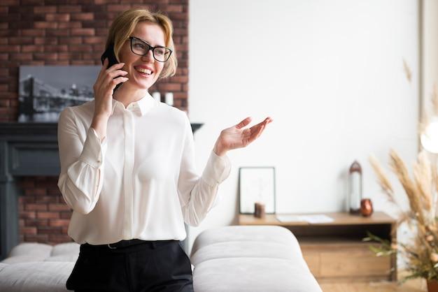Szczęśliwa blond biznesowa kobieta opowiada na telefonie