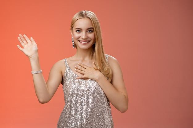 Szczęśliwa blond dziewczyna przywitaj się, przedstaw się, chłopak, przyjaciele, podnieś rękę, machając, witaj, gest naciśnij dłoń klatka piersiowa szczery uśmiechnięty szeroko mówiąc prawdę przysięgam, obiecuję zachować sekret przyjazne spojrzenie aparatu.
