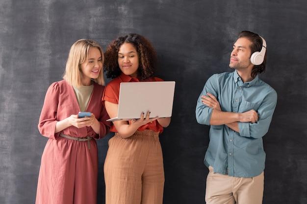 Szczęśliwa blond dziewczyna z smartphone patrząc na wyświetlacz laptopa trzymanego przez jej przyjaciela rasy mieszanej, jednocześnie stojąc przez młodego mężczyznę w słuchawkach