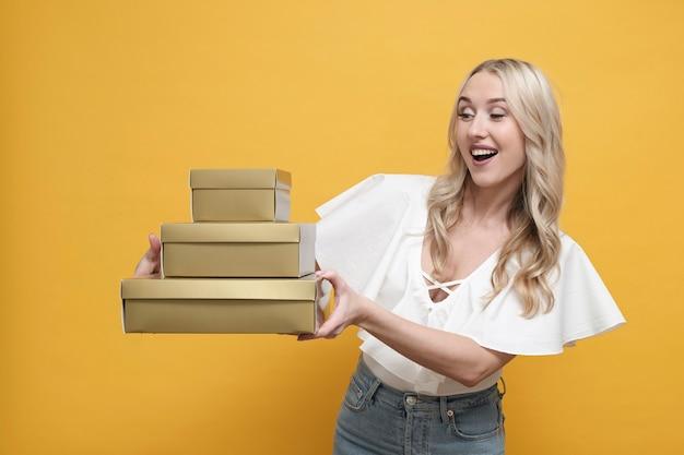 Szczęśliwa blond europejska kobieta trzyma paczkę prezentów pudełka w białej bluzce. skopiuj miejsce