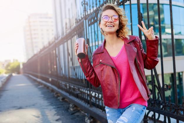 Szczęśliwa blond kobieta pozuje na nowoczesnych ulicach, pije kawę lub cappuccino. stylowy jesienny strój, skórzana kurtka i dzianinowy sweter. różowe okulary przeciwsłoneczne.