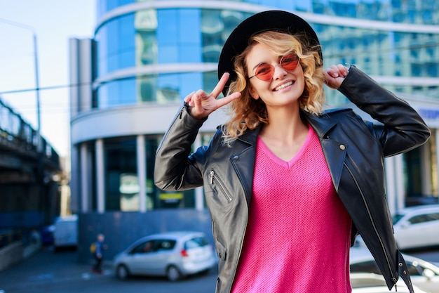 Szczęśliwa blond kobieta pozuje na nowoczesnych ulicach. stylowy jesienny strój, skórzana kurtka i dzianinowy sweter. różowe okulary przeciwsłoneczne.