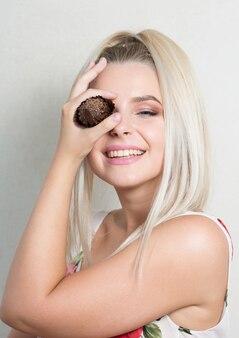 Szczęśliwa blond kobieta trzyma aromatyczną czekoladową babeczkę