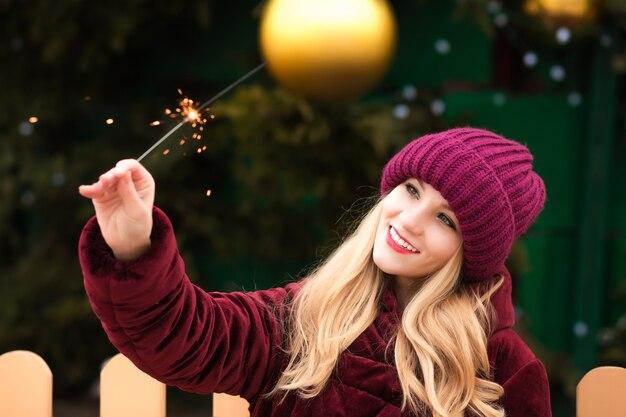 Szczęśliwa blond kobieta ubrana w czerwony dzianinowy kapelusz i ciepły płaszcz trzymający świecące ognie na choince