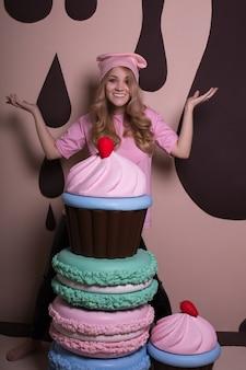 Szczęśliwa blond kobieta ubrana w różową czapkę i t shirt bawi się z dużymi makaronikami i babeczkami w studio