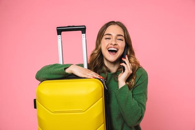Szczęśliwa blond kobieta ubrana w zielony sweter pozuje z bagażem i rozmawia przez smartfona z zamkniętymi oczami na różowej ścianie