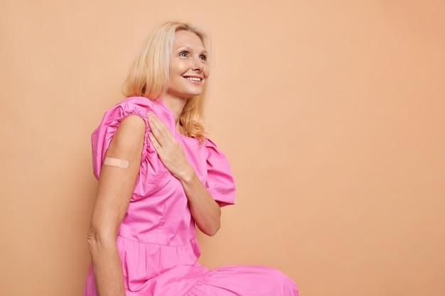 Szczęśliwa blond kobieta w średnim wieku otrzymała szczepienie, ciesząc się, że jest w pełni chroniona, nie może nosić maski zapewnia silne wzmocnienie pozycji ochronnych na brązowej ścianie