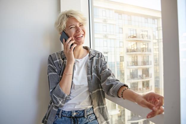 Szczęśliwa blond kobieta z krótkimi blond włosami, ubrana w zwykłe ubrania, stojąca przy oknie i trzymająca telefon komórkowy na dłoni, patrząc na bok i śmiejąca się
