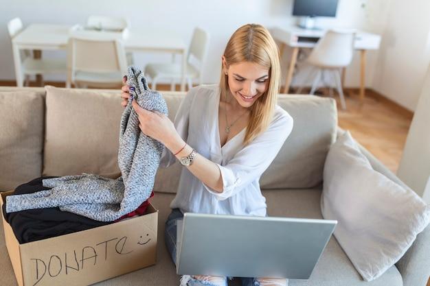 Szczęśliwa blond młoda kobieta siedzi na kanapie przyklejone ubrania w pudełku darowizny w domu, opiekuńcza biracial wolontariuszka wkłada odzież do opakowania kartonowego, przekazuje potrzebującym ludziom, ponowne wykorzystanie, koncepcja recyklingu