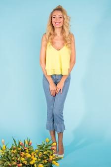 Szczęśliwa blond młoda kobieta z tulipanów na niebieskiej ścianie, portret pełnej długości