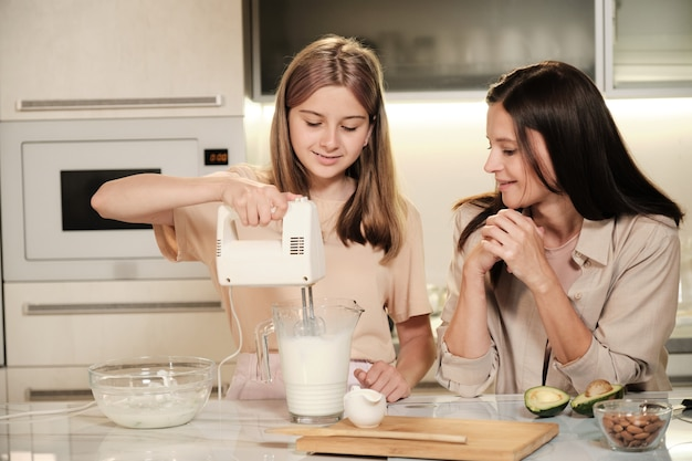 Szczęśliwa blond nastolatka trzyma mikser elektryczny lub mikser w dużym szklanym dzbanku ze świeżym mlekiem i owocami, pomagając mamie w gotowaniu