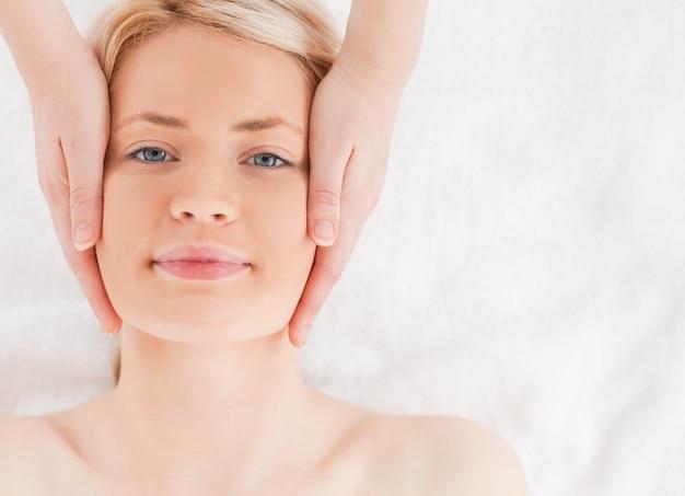 Szczęśliwa blond włosy kobieta dostaje masaż na jej twarzy
