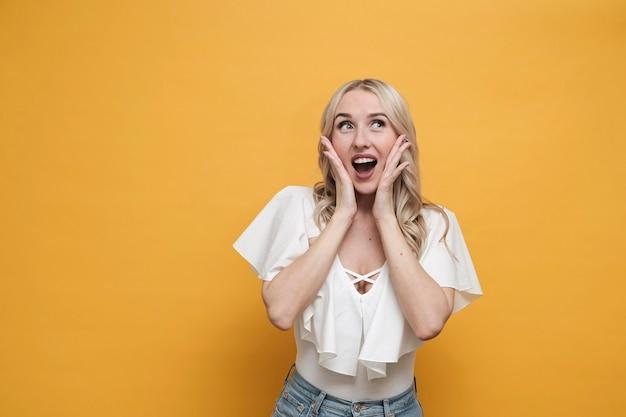 Szczęśliwa blond zdziwiona kobieta w białej bluzki pozyci. skopiuj miejsce