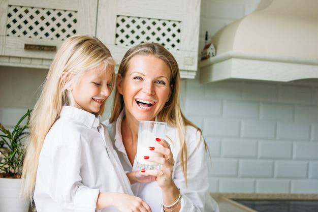 Szczęśliwa blondynka długie włosy mama i córka pije mleko w kuchni, zdrowy styl życia