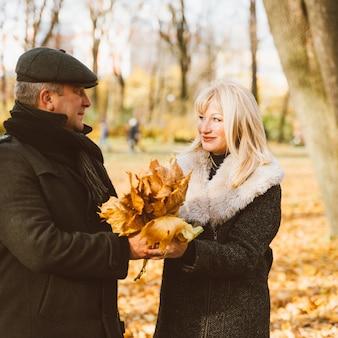 Szczęśliwa blondynka dojrzała kobieta i przystojny mężczyzna w średnim wieku brunetka chodzić po parku, patrząc na siebie