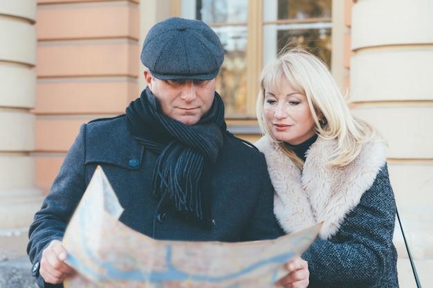 Szczęśliwa blondynka dojrzała kobieta i przystojny mężczyzna w średnim wieku brunetka podróżować i cieszyć się życiem