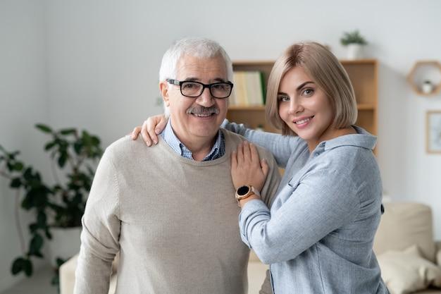 Szczęśliwa blondynka dorywczo młoda kobieta obejmując swojego wesołego starszego ojca, patrząc na kamery w domu