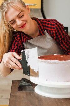 Szczęśliwa blondynka gotuje ciasto z białą śmietaną na drewnianym stole w kuchni