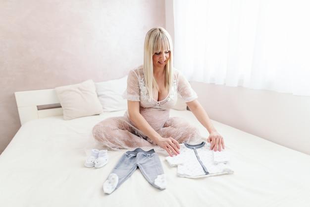 Szczęśliwa blondynka kaukaski kobieta w ciąży patrząc na ubrania dziecka, siedząc na łóżku ze skrzyżowanymi nogami w sypialni.