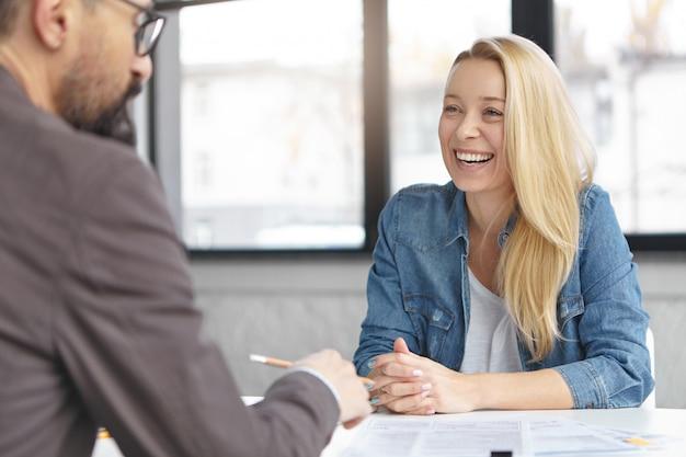 Szczęśliwa blondynka menedżerka rozmawia z kolegą