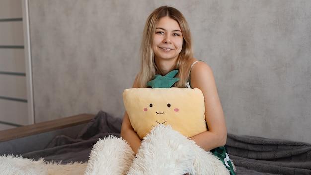 Szczęśliwa blondynka rano przytula żółtą ananasową poduszkę. koncepcja szczęśliwego poranka