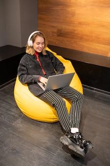 Szczęśliwa blondynka spokojny dziewczyna siedzi w miękkim, wygodnym fotelu z żółtej skóry, słuchając muzyki i przeglądając internet
