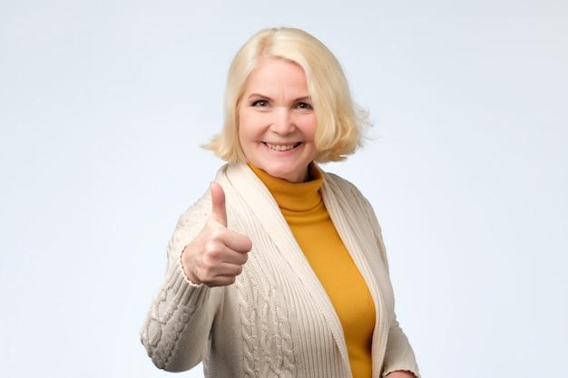 Szczęśliwa blondynka starszy kobieta pokazuje aprobaty