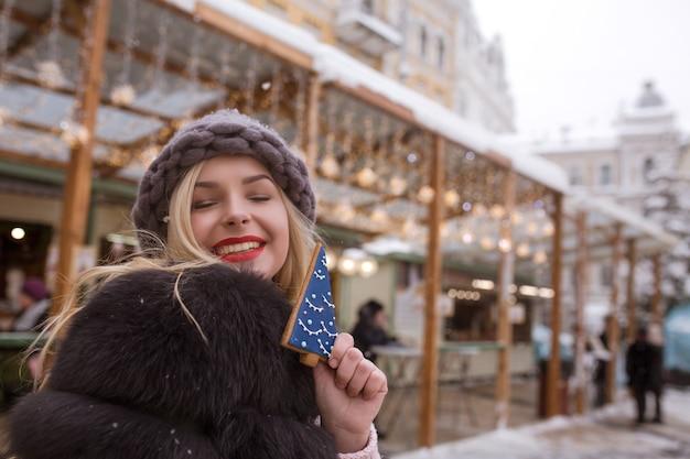 Szczęśliwa blondynka trzymająca pikantne pierniki na tle lekkiej dekoracji na jarmarku bożonarodzeniowym w kijowie