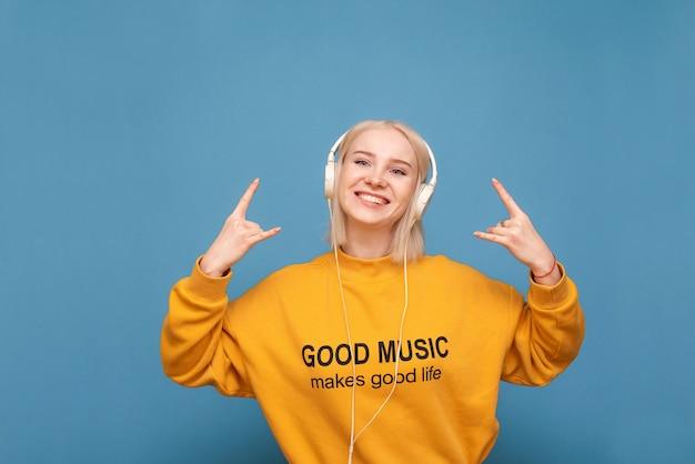 Szczęśliwa blondynka w pomarańczowej bluzie i słuchawkach jest na niebiesko, słucha muzyki i pokazuje znak heavy metalu