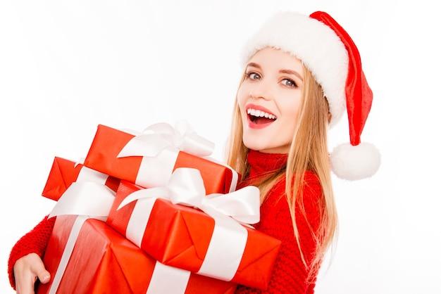 Szczęśliwa blondynka w santa's hat trzyma prezenty na nowy rok