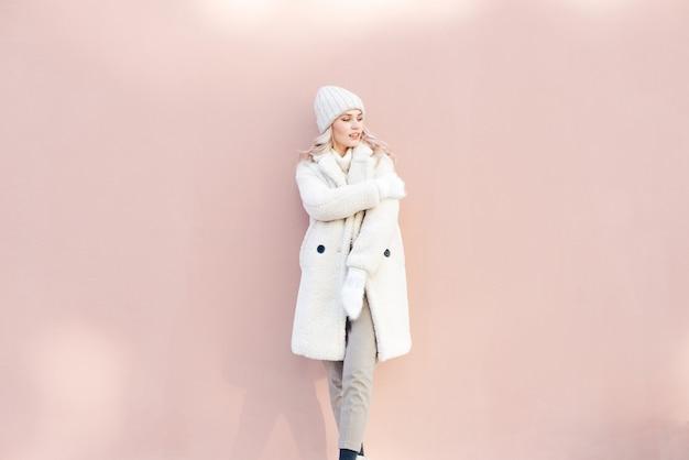 Szczęśliwa blondynki dziewczyna w białych zim ubraniach pozuje przeciw różowej ścianie.